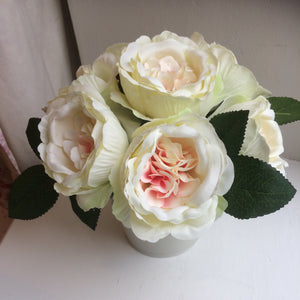 A simple bunch of artificial roses in cream container