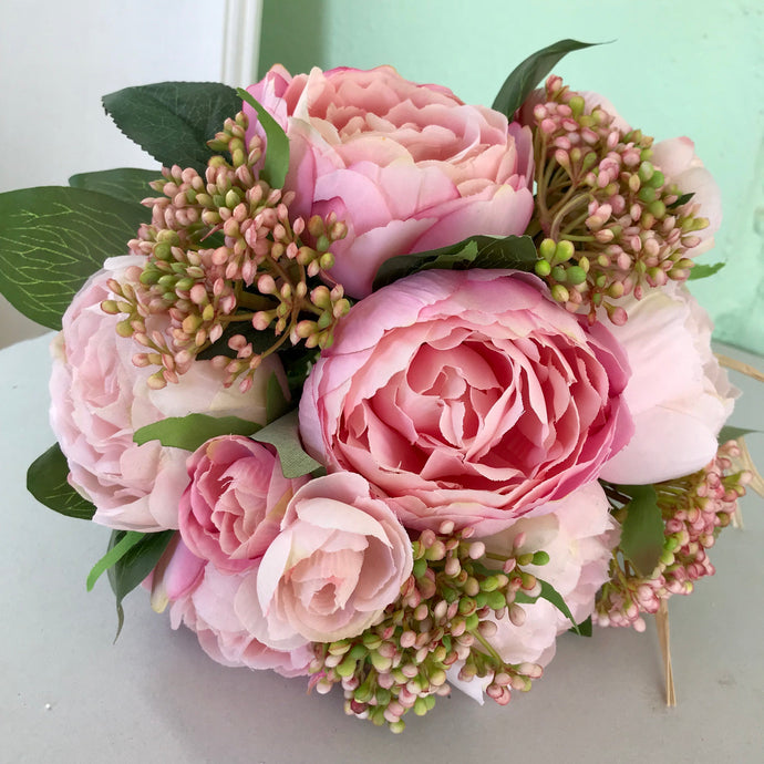 - A brides bouquet featuring pink peonies
