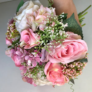 A brides bouquet of pink artificial flowers