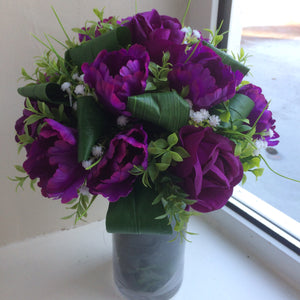 Flower arrangement of artificial purple roses in glass vase