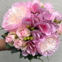 A wedding bouquet featuring pink roses and hydrangea