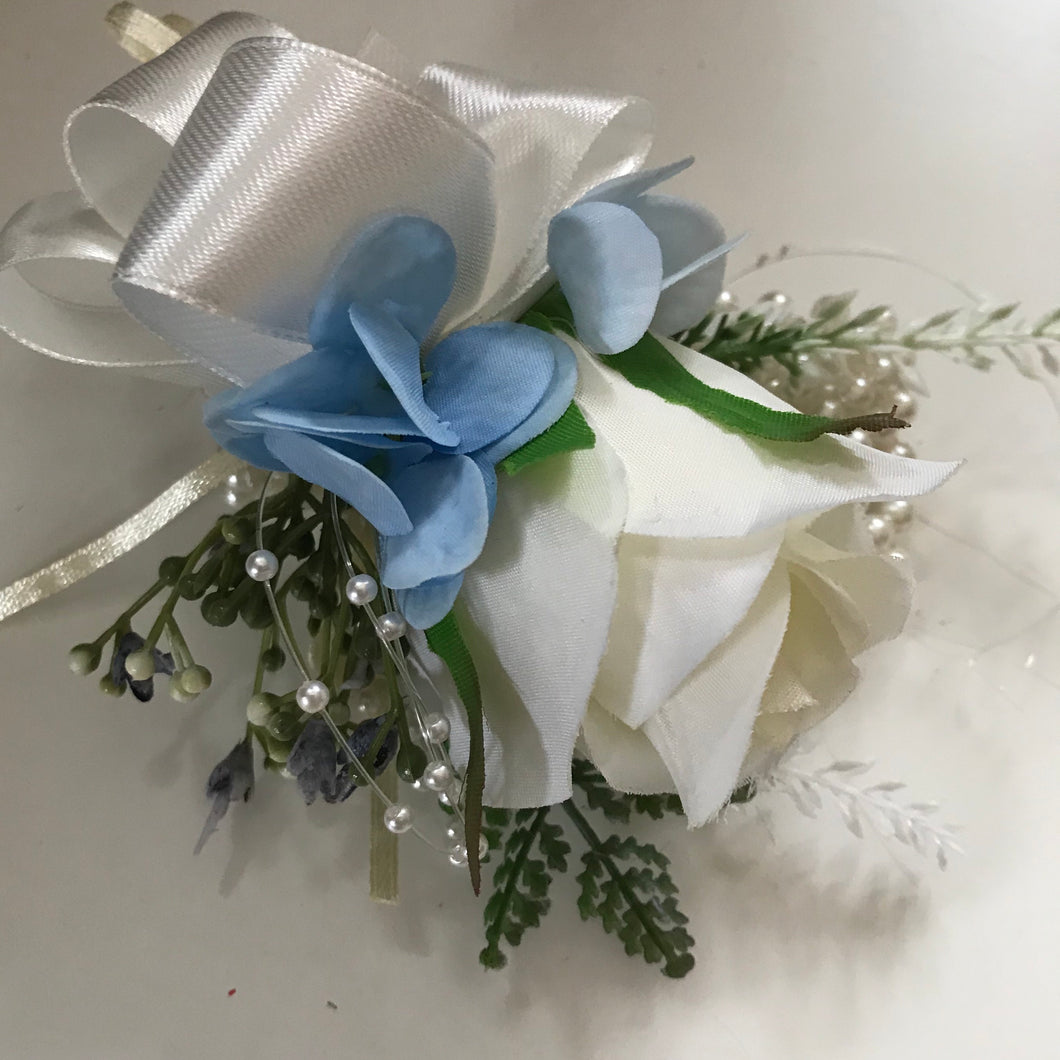 A wrist corsage featuring Ivory and blue flowers