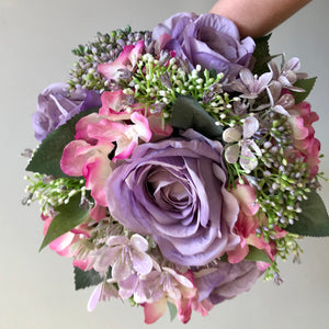 a wedding bouquet of lilac and pink silk flowers
