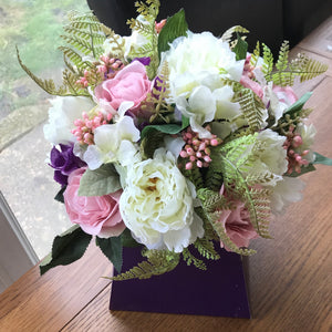 A faux silk flower arrangement in purple bouquet box