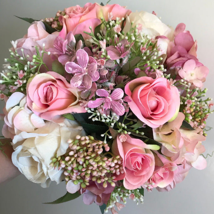 - A brides bouquet of pink artificial flowers