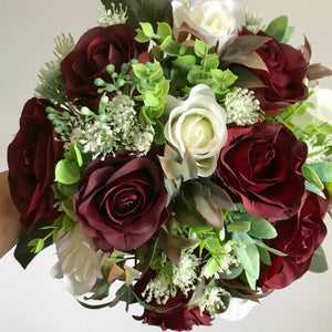 An artificial wedding bouquet of ivory and burgundy roses