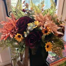 An arrangement of peach orange and burgundy flowers in black plastic vase