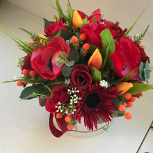 A flower arrangement of red artificial flowers in hat box