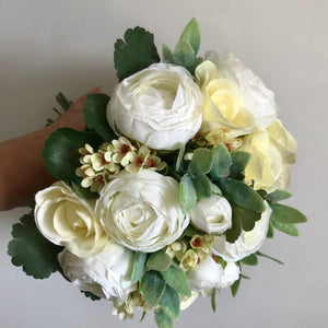 A wedding bouquet of ivory ranunculus and lemon roses