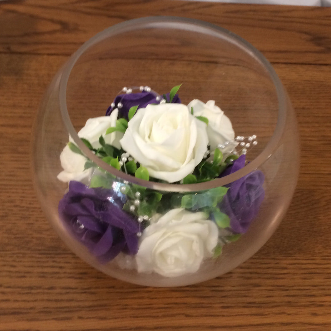 An arrangement of roses in glass fishbowl