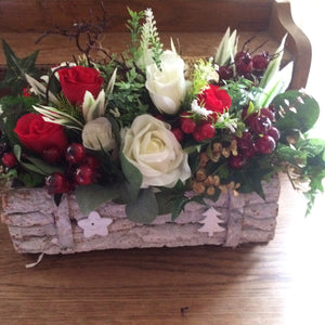 An arrangement of Christmas flowers in white washed log roll