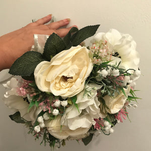 A brides bouquet of artificial ranunculus and anemone flowers