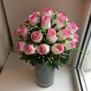 a glass vase of pink roses