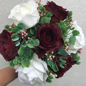 an artificial wedding bouquet of burgundy and ivory flowers