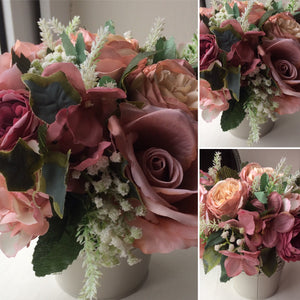 A flower arrangement of roses, ranunculus and hydrangea