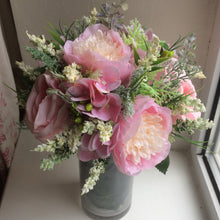 A flower arrangement of artificial pink peonies & roses in glass vase