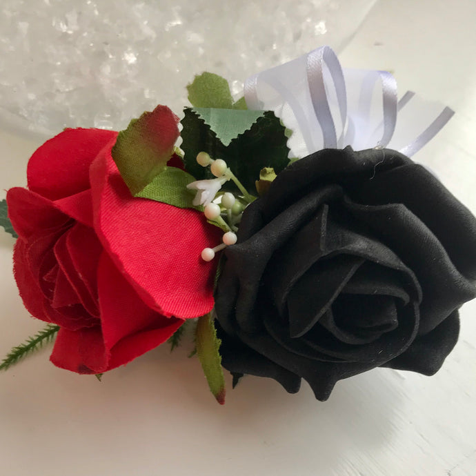 A flower corsage featuring black and red foam roses