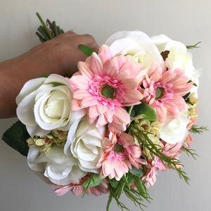a wedding bouquet of ivory roses and pink gerbera