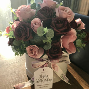 a flower arrangement of artificial roses in hat box