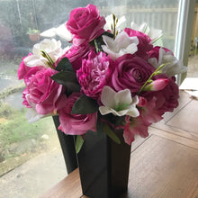 A large handtied flower arrangement of deep pink and ivory silk flowers