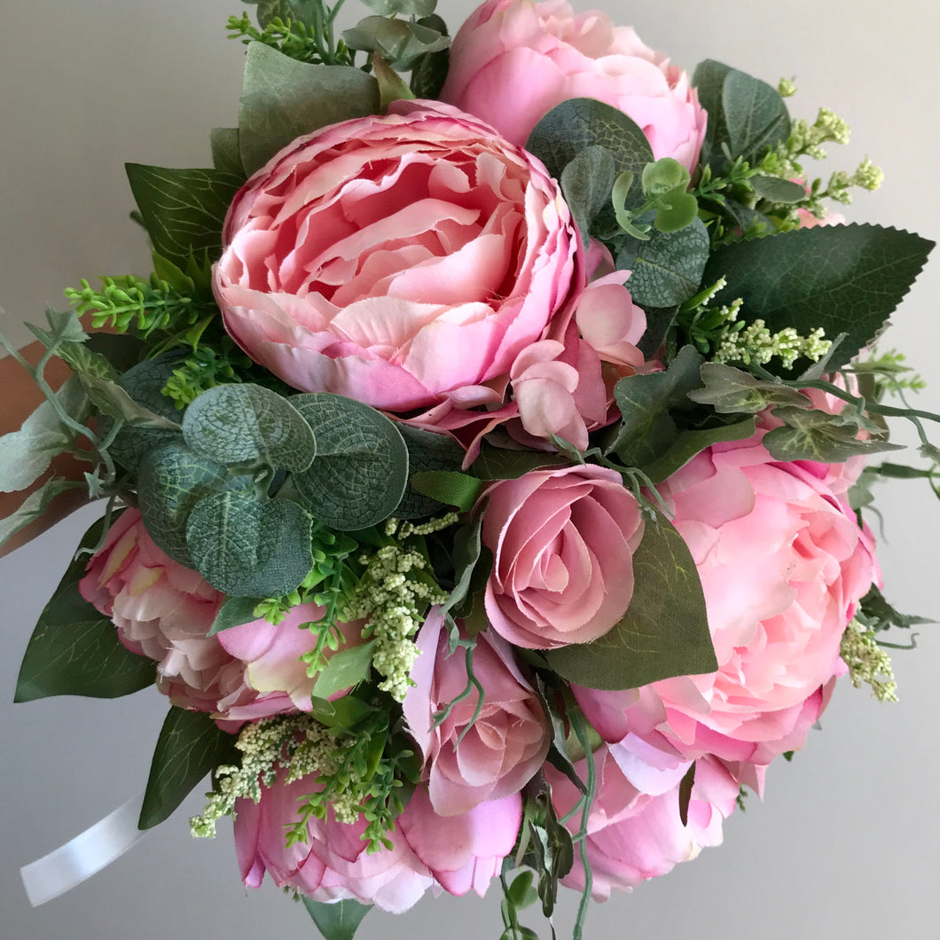 A wedding bouquet featuring pink peonies and foliage