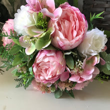 A brides bouquet of artificial pink peonies and ivory roses