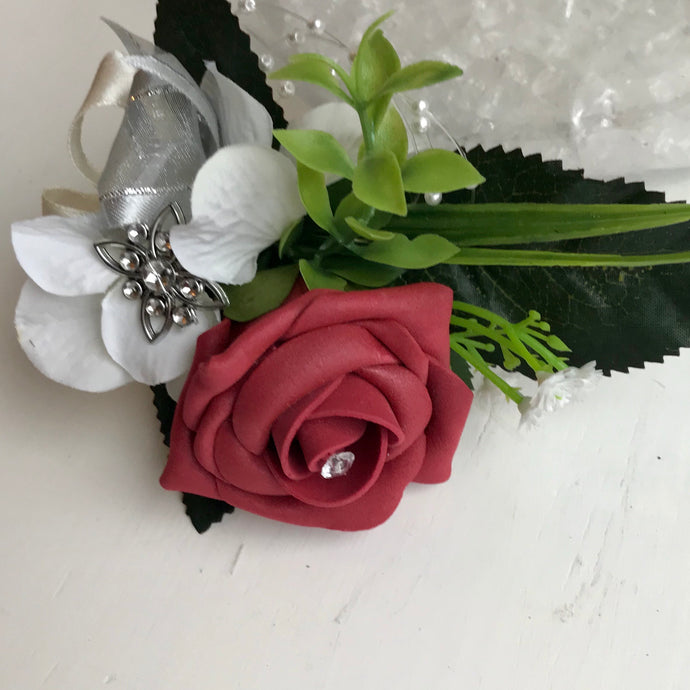 A flower corsage featuring burgundy foam roses and hydrangea