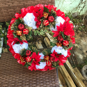 a memorial christmas wreath featuring baubles, cones and poinsettia