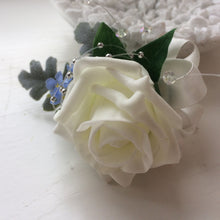 An artificial wedding buttonhole featuring an ivory rose & blue forgetmenots