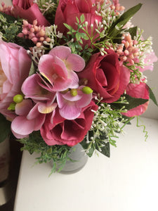 A flower arrangement of silk flowers in class cylinder