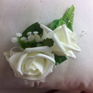 an artificial corsage featuring ivory foam roses