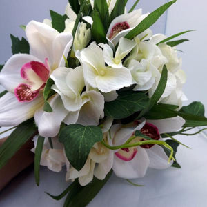 A wedding bouquet of ivory and pink artificial silk flowers