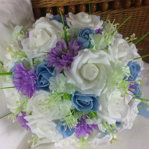 a brides bouquet of lilac, white and blue artificial flowers