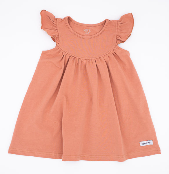 solid sunset hue flutter sleeve pearl dress in the most perfect shade of rosey peach.