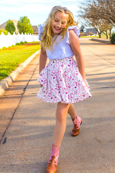 all knit circle skirt with wide waistband and a plum floral pattern on a white background, modeled by a girl with a white tank and amazing Nathalie Verlinden booties