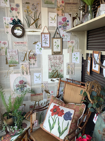 Bamboo/rattan chair with floral pillow and small terra cotta pots with flowers in front of a custom created floral wall behind it.