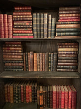 Three shelves filled with various vintage French leather bound books.  There is a mixture of colors - red, green, tans, and black.