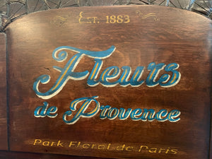 close up of Fleurs de Provence, Est 1883, Park floral de Paris, hand-painted wood sign