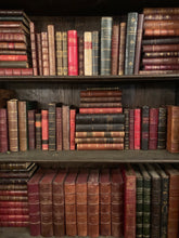 Three shelves filled with various vintage French leather bound books.  The colors range from brown, green, red, and black.