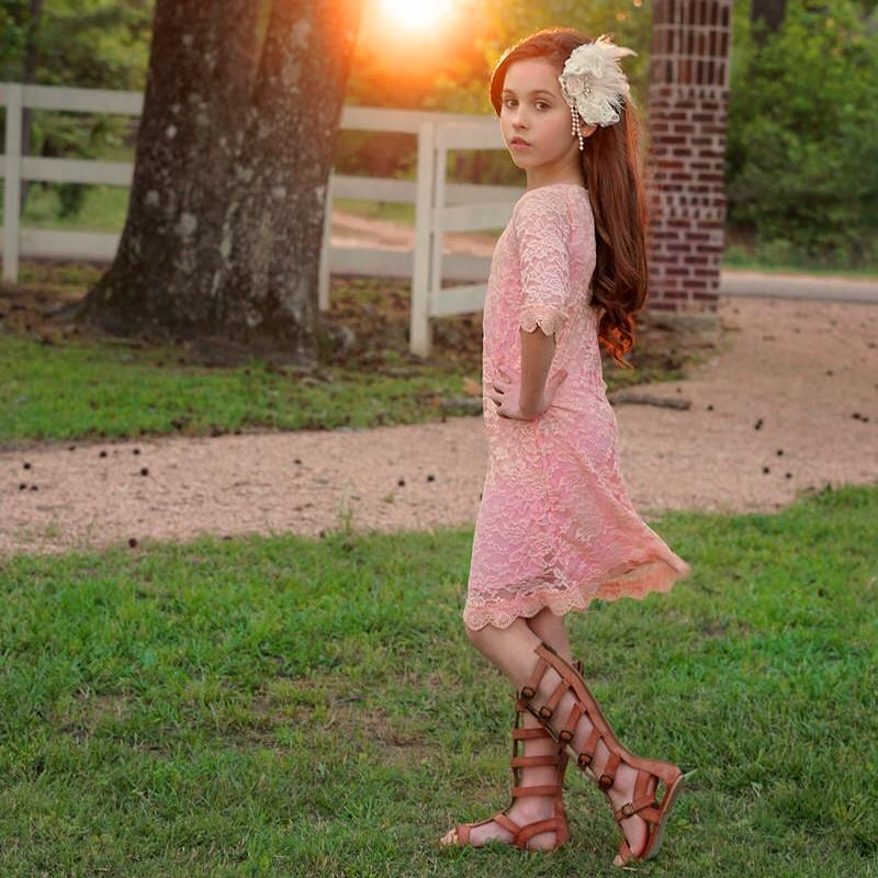 Little girl wearing peach lace dress, gladiator sandals, and floral hair piece