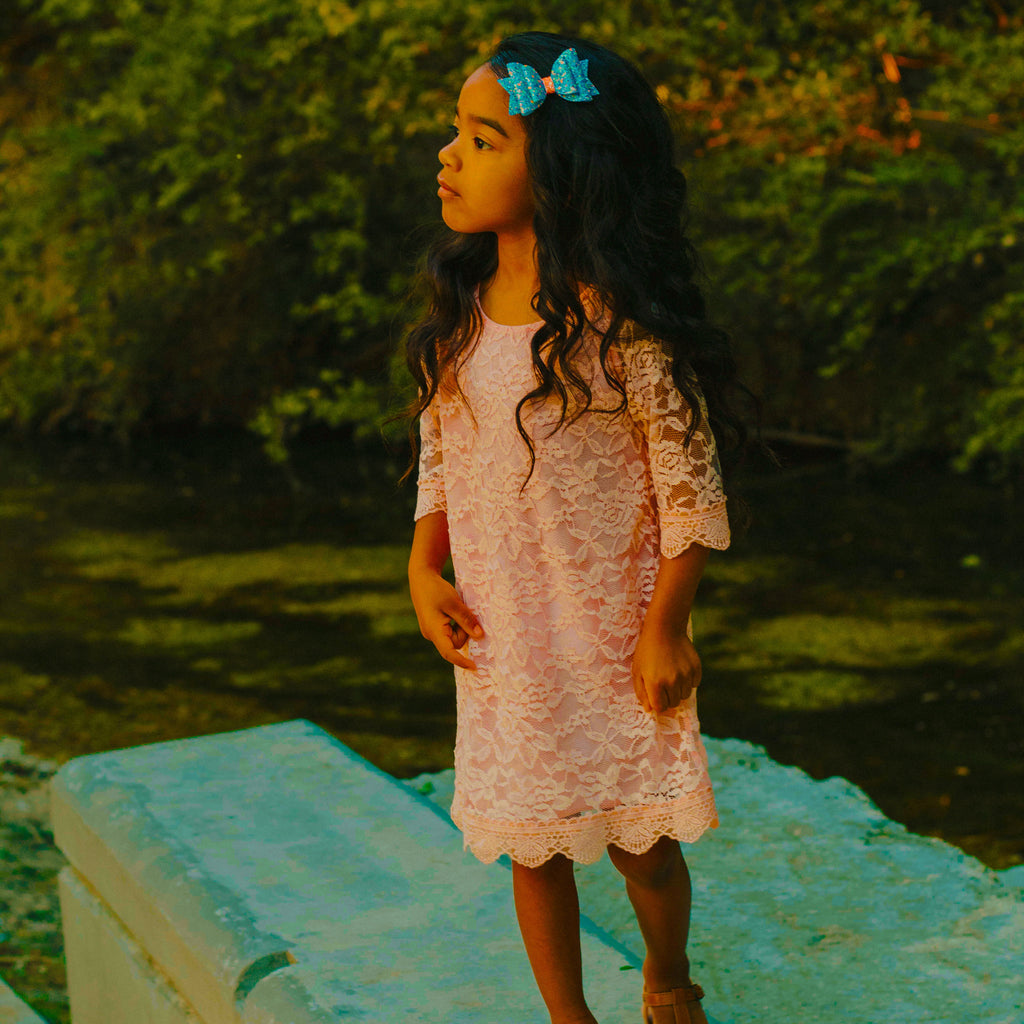 Little girl wearing peach lace dress and blue bow