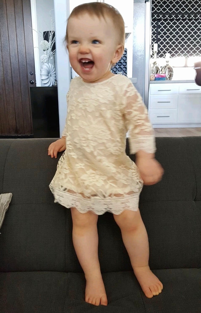 Baby girl wearing ivory lace dress