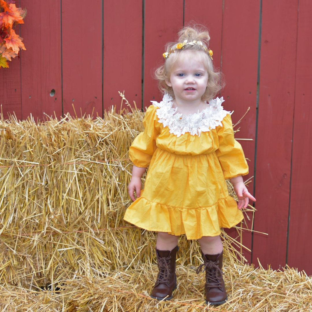 Baby girl in our off shoulder peasant dress in harvest gold