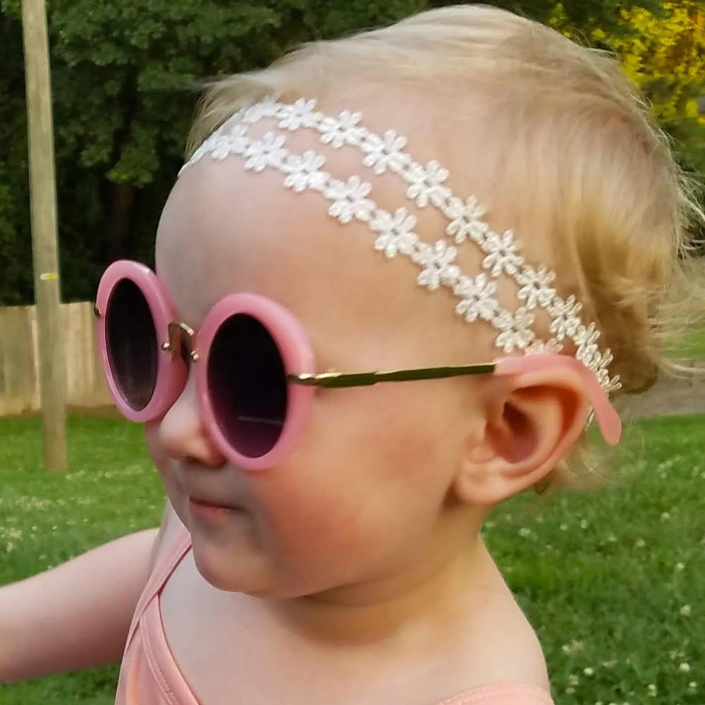 Baby girl wearing our retro headband in white flowers and our pink retro sunglasses
