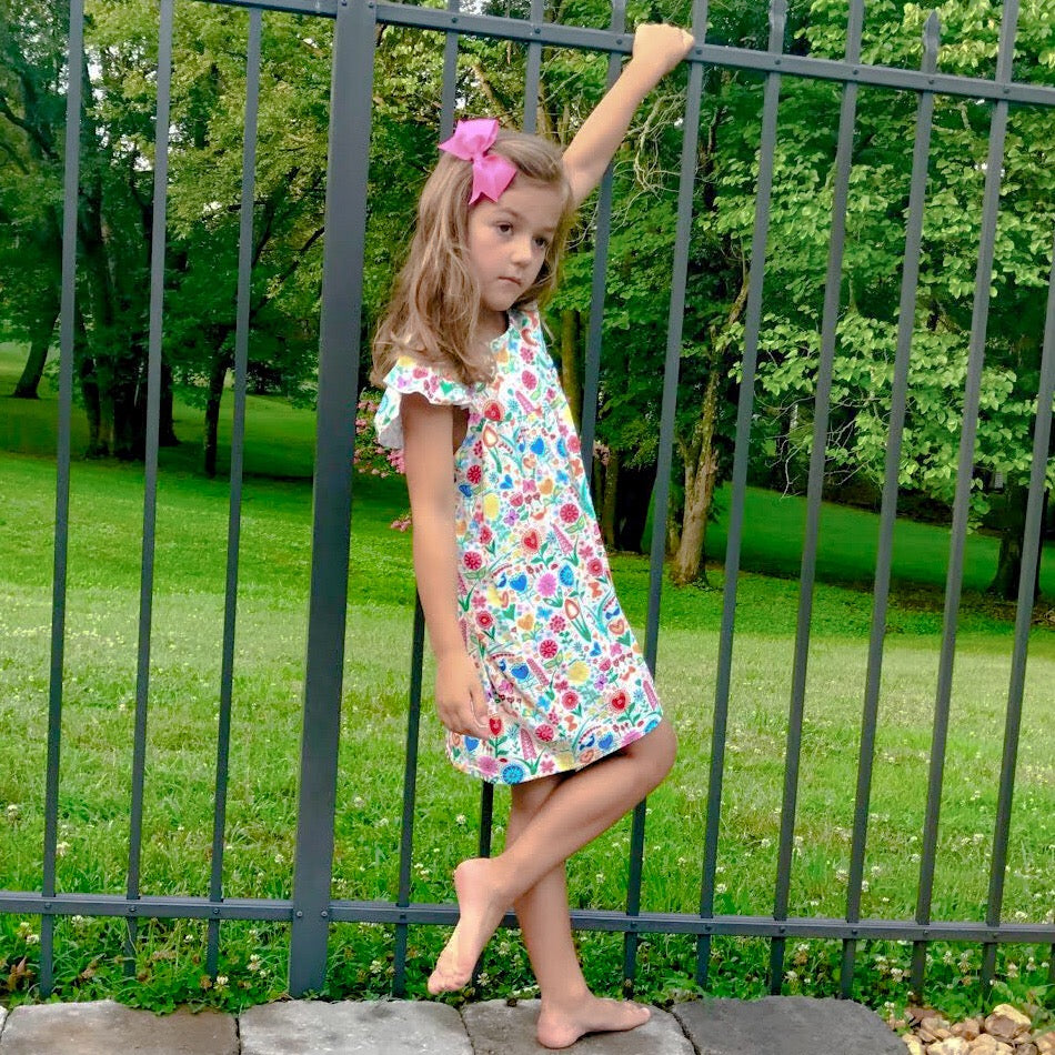 LIttle girl hanging out by the pool fence in our dutch garden print flutter sleeve lap dress