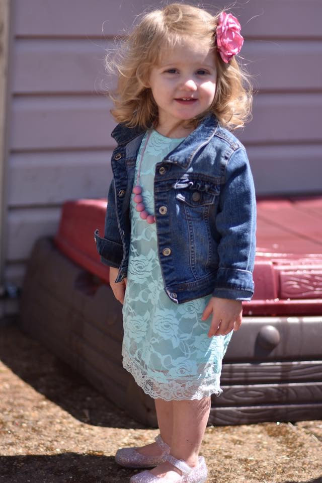 Baby girl wearing aqua lace dress, pink flower in her hair, and denim jacket