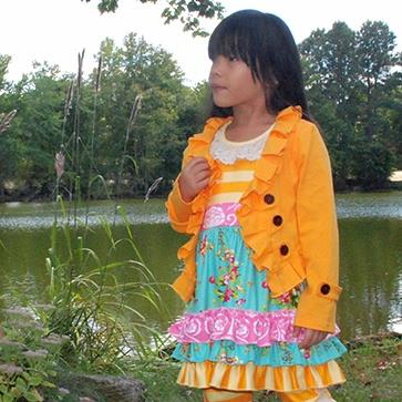 Little girl in aqua, marigold orange, and pink ruffle dress and leggings, wearing the marigold orange ruffle double breasted cropped cardigan