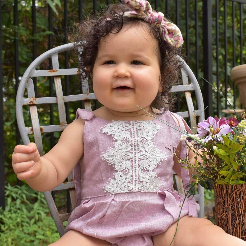 Baby girl in dusty pink linen romper with rabbit ear headband