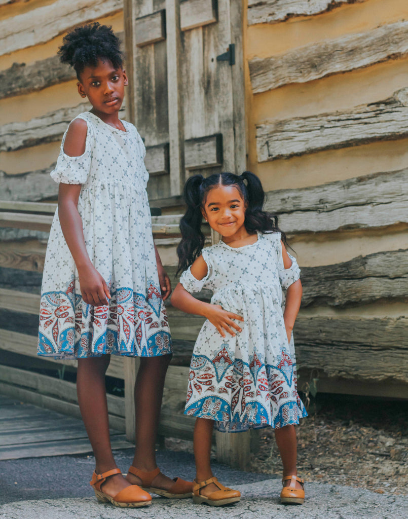 Two little girls wearing our boho cold shoulder dress