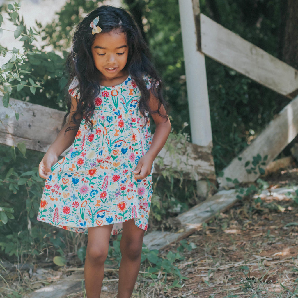 LIttle girl wearing our dutch garden print flutter sleeve lap dress in a rustic location